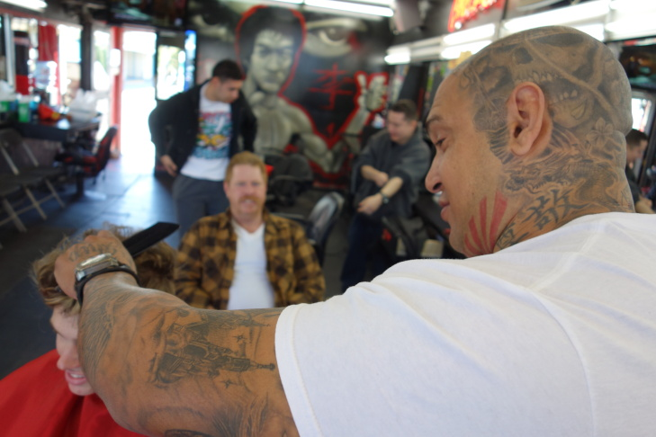 Charlie Ortiz, owner of Charlie's Chop Shop in Bell, gives Joshua Bolin a haircut under the watchful eye of his father, Red Bolin, and a mural of Bruce Lee