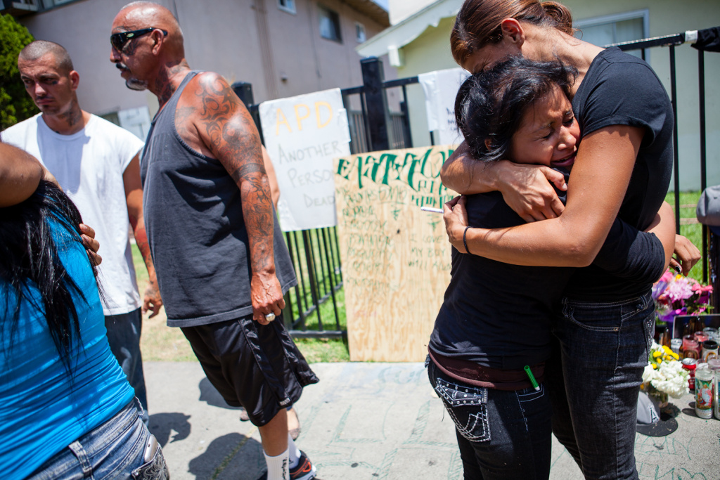 File photo: Perla Castillo (right) hugs Daisy, 18, at the scene of Manuel Diaz's shooting in Anaheim, CA in 2012. Both were good friends of Diaz. The ACLU issued a report on Nov. 20, 2017 saying the Anaheim Police Department has failed to reduce the rate of officer-involved deaths since reforms were enacted after 2012.