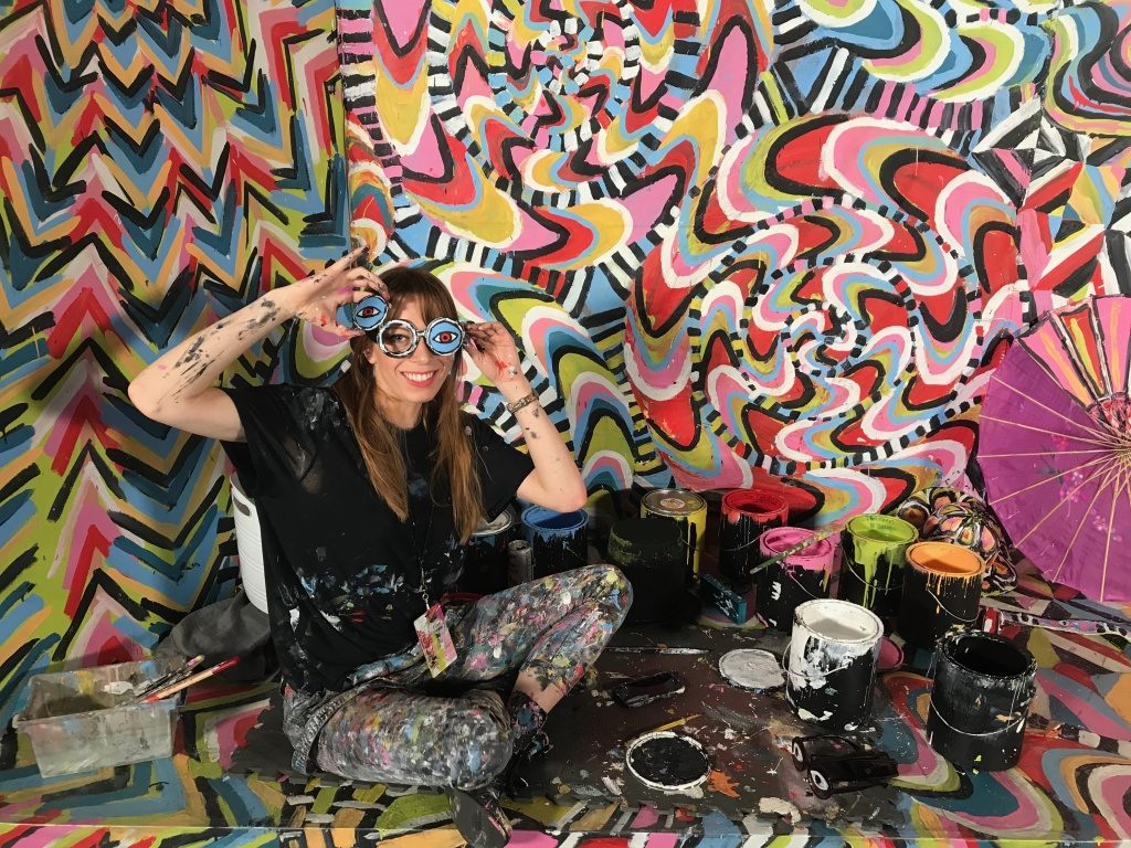Artist Alexa Meade shows off her prop glasses in her room, Become the Masterpiece. Visitors put on clothes and costume props to become part of a psychedelic backdrop.