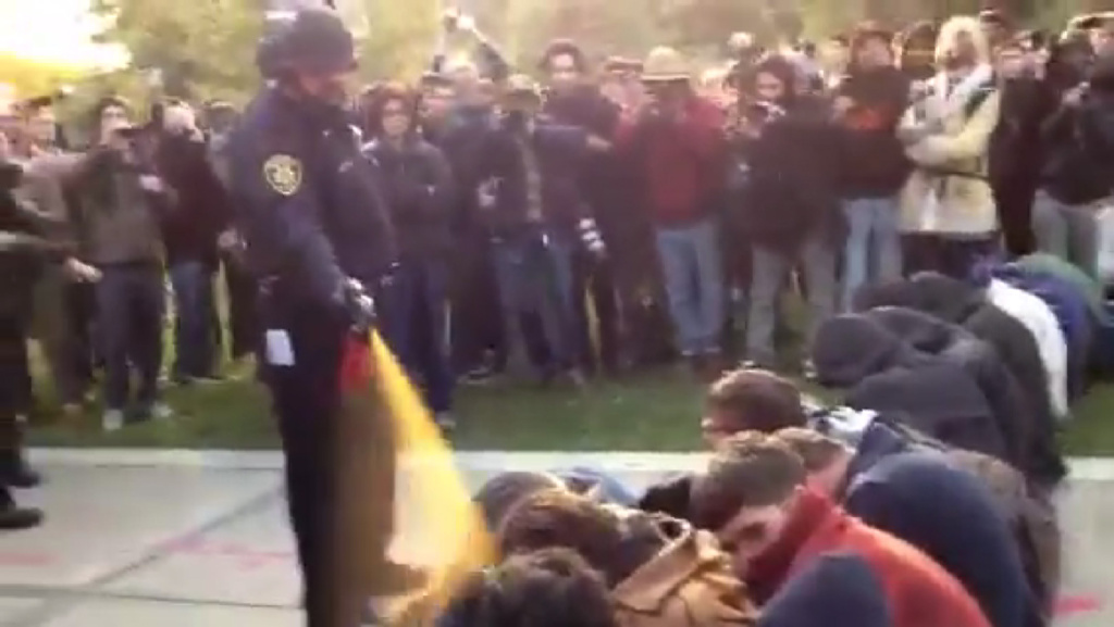 In this image made from video, a police officer uses pepper spray as he walks down a line of Occupy demonstrators sitting on the ground at the University of California, Davis on Friday, Nov. 18, 2011. The video - posted on YouTube - was shot Friday as police moved in on more than a dozen tents erected on campus and arrested 10 people, nine of them students.