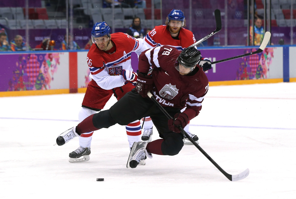 Vitalijs Pavlovs #79 of Latvia handles the puck against Patrik Elias #26 of Czech Republic in the second period during the Men's Ice Hockey Preliminary Round Group C game on day seven of the Sochi 2014 Winter Olympics at Bolshoy Ice Dome on February 14, 2014 in Sochi, Russia.
