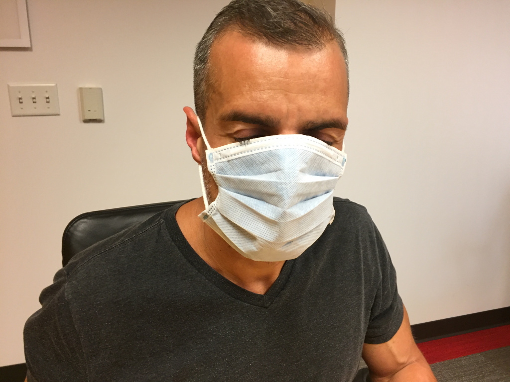 A Martinez tries on a surgical mask.