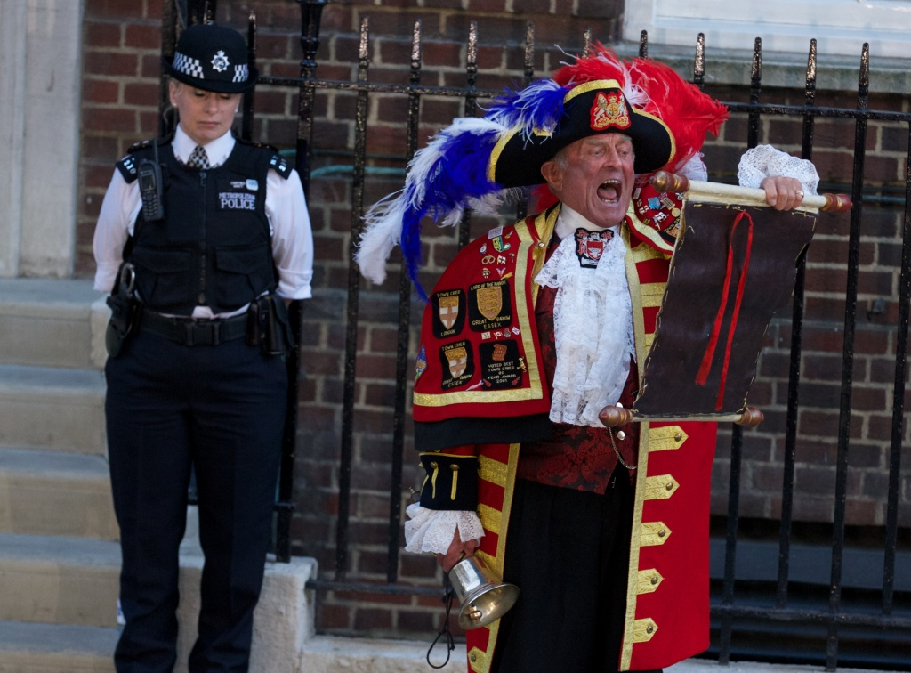 A Town Crier reads an announcement about the birth of a baby boy to Prince William and Catherine, Duchess of Cambridge, outside the Lindo Wing of St Mary's Hospital in London, on July 22, 2013.