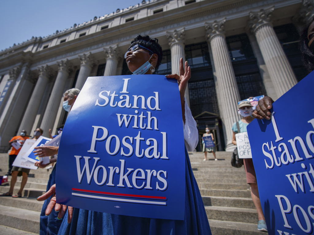 Retired postal worker Glenda Morris protests postal cutbacks on Aug. 25, 2020, in New York. African Americans make up 27 percent of the Postal Service, about twice their share of the overall workforce.