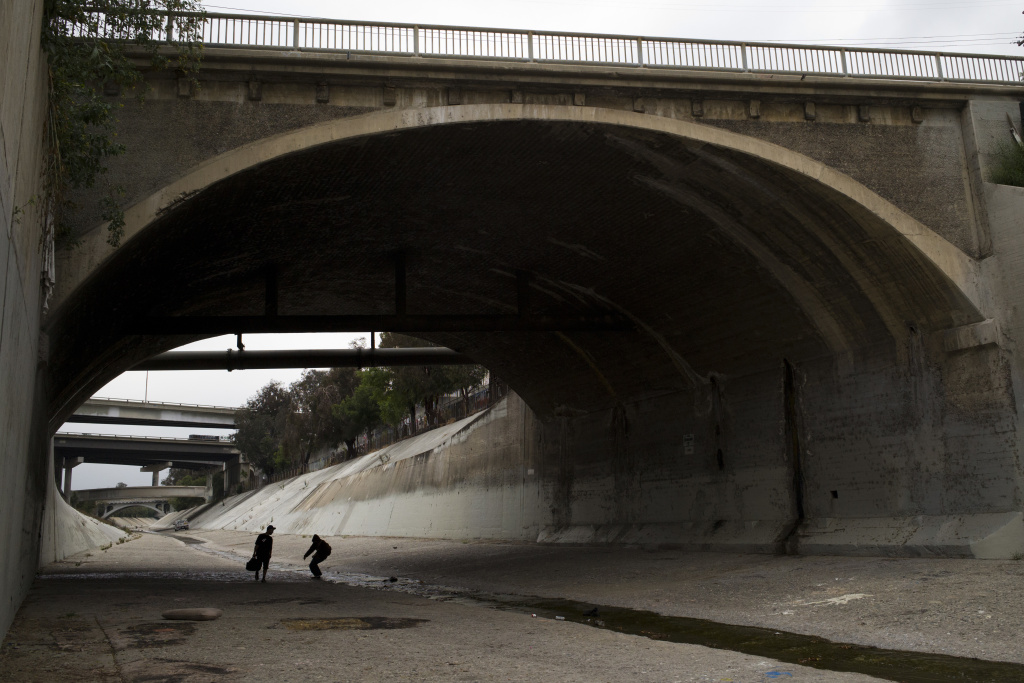 Two homeless men walk under a bridge along the Los Angeles River, where almost extinct forms of American hieroglyphics known as hobo graffiti were discovered.