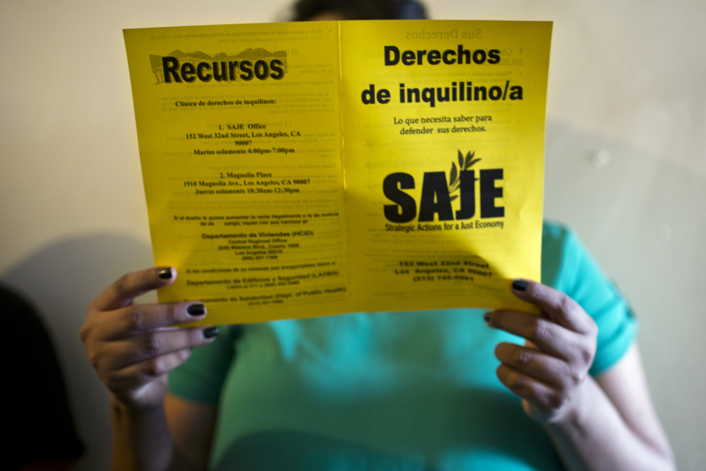 Elizabeth Tovar reads a brochure on tenant rights from Strategic Actions for a Just Economy during a tenant meeting on Friday, July 31, 2015 in her East Washington Boulevard apartment building.