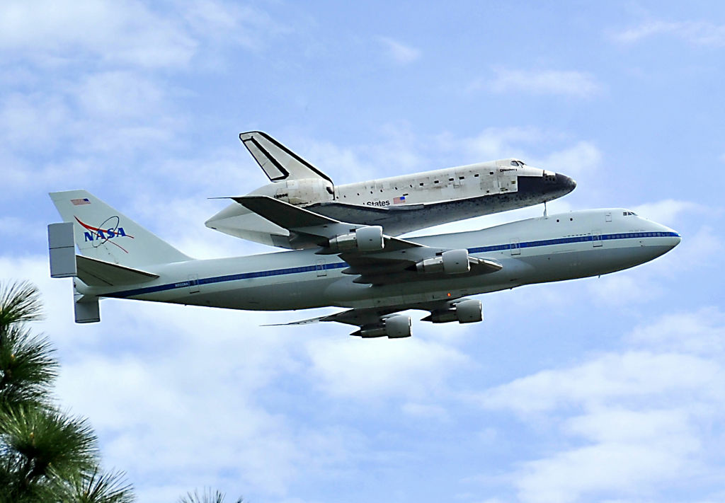 The Space Shuttle Discovery, aboard a specially modified NASA Boeing 747, flies over the Washington, DC, April 17, 2012, as seen from Arlington, Virginia.