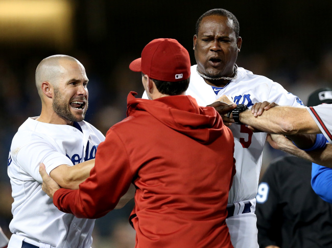 Manager Don Mattingly of the Los Angeles Dodgers pushes down coach Alan Trammell #3 of the Arizona Diamondbacks during as Diamondbacks coach Matt Williams tries to restrain Mattingly a bench clearing brawl in the seventh inning at Dodger Stadium on June 11, 2013 in Los Angeles.