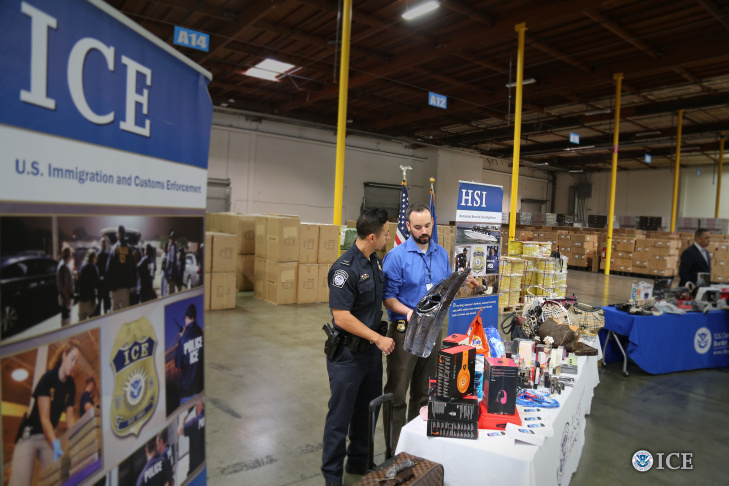 A CBP Officer and an ICE/HSI special agent holding a seized counterfeit car grill on display in front of the media at the Trade Enforcement Coordination Center.