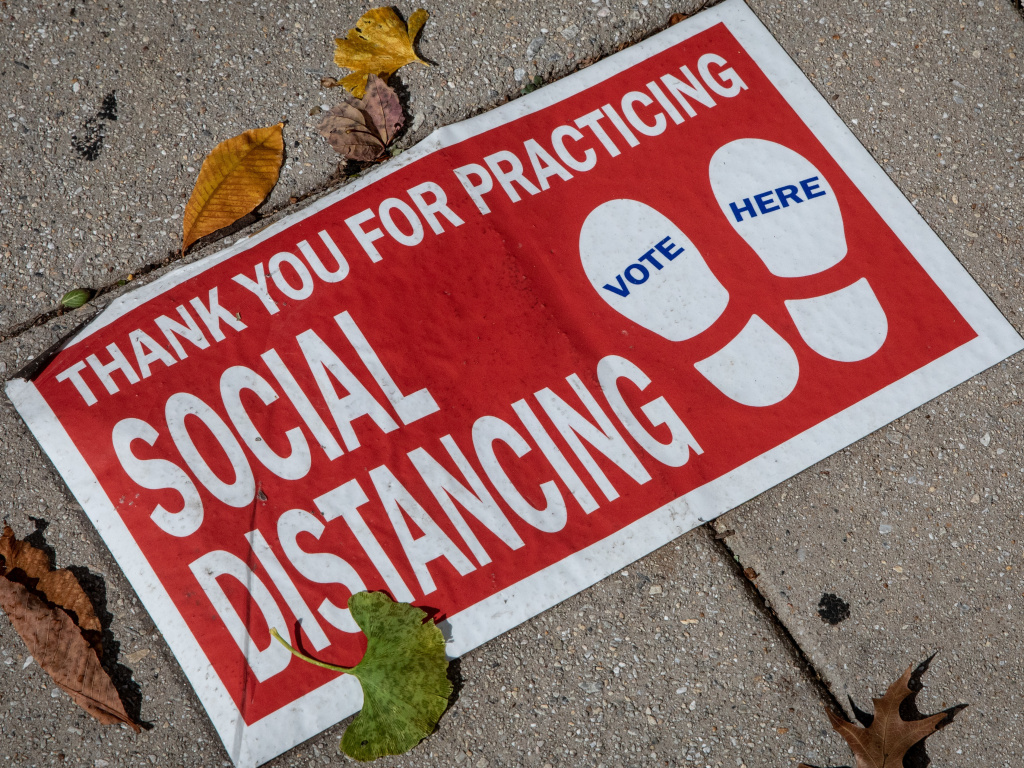 A social distancing sign on the ground.