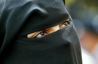 A veiled Palestinian woman looks on as she attends a protest in Gaza City, Gaza Strip. Thousands of Palestinians attended the protest in Gaza to commemorate the 28th anniversary of Land Day.