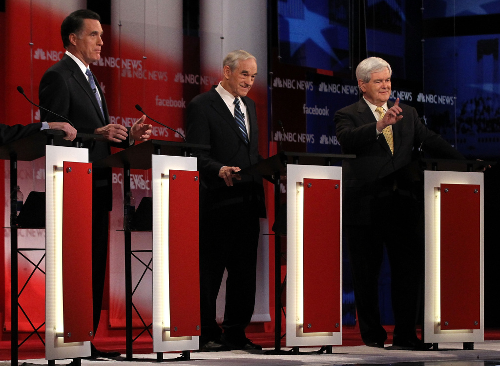 Republican presidential candidates, former Massachusetts Gov. Mitt Romney (L) debates with former Speaker of the House Newt Gingrich (R) as U.S. Rep. Ron Paul (R-TX) (C) listens during the NBC News Facebook Debate on 'Meet the Press' January 8, 2012 at the Capitol Center for the Arts in Concord, New Hampshire.