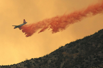 An air tanker drops fire retardant on a ridge ahead of a fast moving fire in the Angeles National Forest August 30, 2009 near Acton.