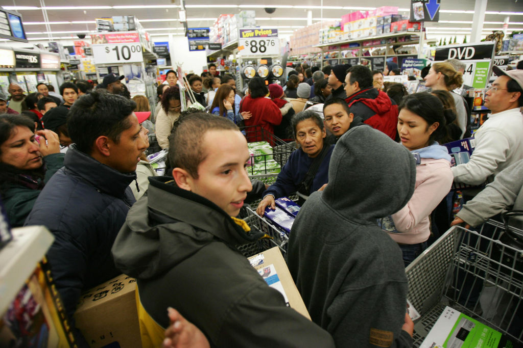 Shoppers try to work their way through the crowd that mobbed the Wal-Mart in Duarte, California, shortly after the retail giant opened its doors at 5 a.m., 25 November 2005, the day after Thanksgiving, also known as 'Black Friday.'