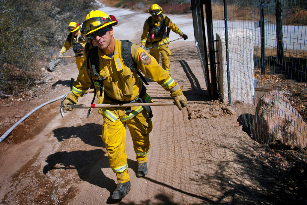 Art Aguilera and his CalFire crew prepare to clear burned brush as the Silver Fire continues to burn in the San Jacinto Mountains near Banning, Calif. on Friday, Aug. 9.