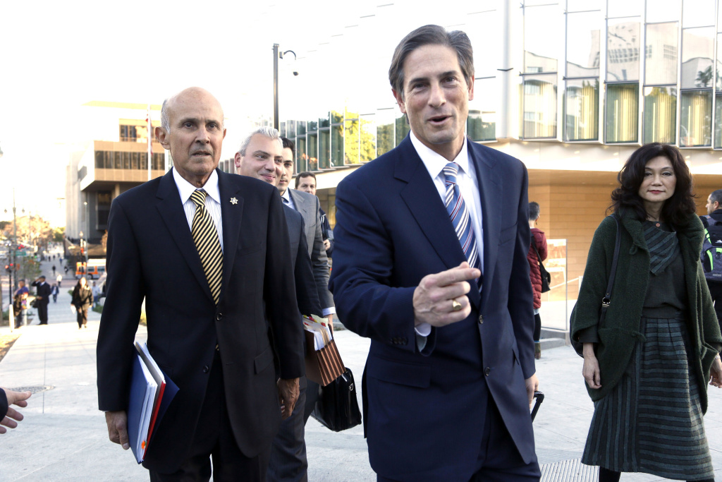 Former Los Angeles County Sheriff Lee Baca, left, his attorney Nathan Hochman, center, and Baca's wife Carol leave federal court in Los Angeles, Monday, Dec. 19, 2016, after the prosecution and defense presented their closing arguments and the case went to the jury.