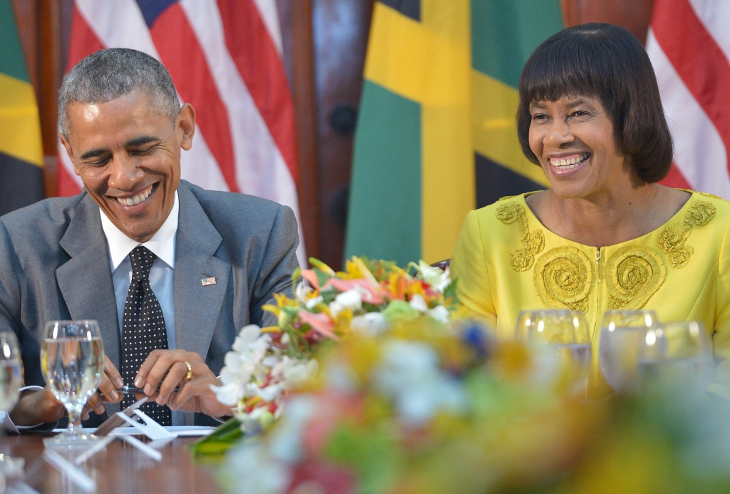 US President Barack Obama (L) shares a laugh with Jamaica's Prime Minister Portia Simpson Miller during a meeting at Jamaica House on April 9, 2015 in Kingston.