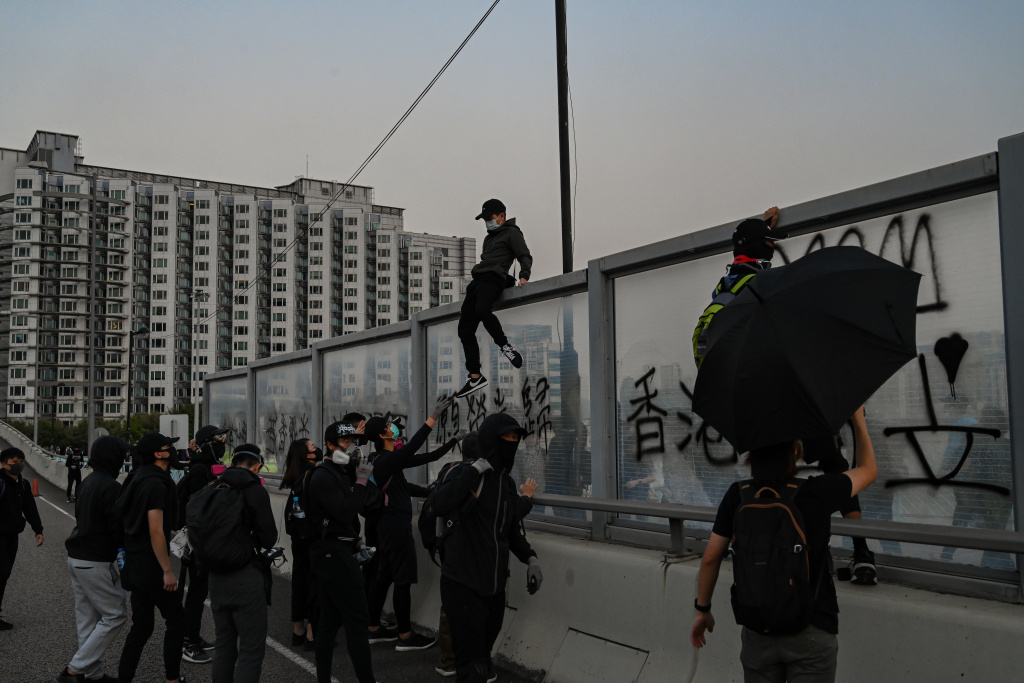 Pro-democracy protesters climb over a highway dividers fleeing from police arrests during a mass rally on December 1, 2019 in Hong Kong, China.