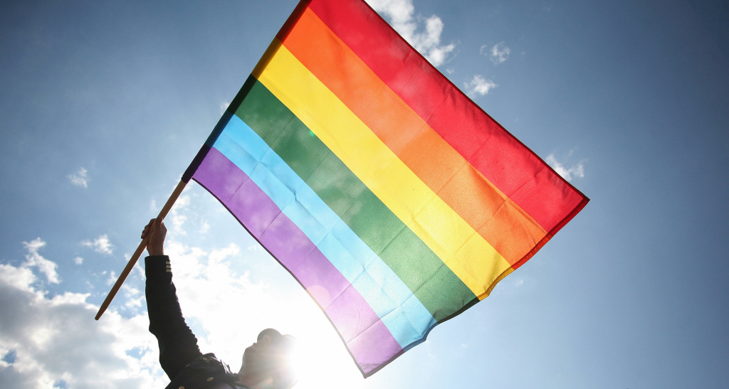 File: A man waves a rainbow flag as he takes part to the Gay Pride parade on June 7, 20008 in Warsaw.