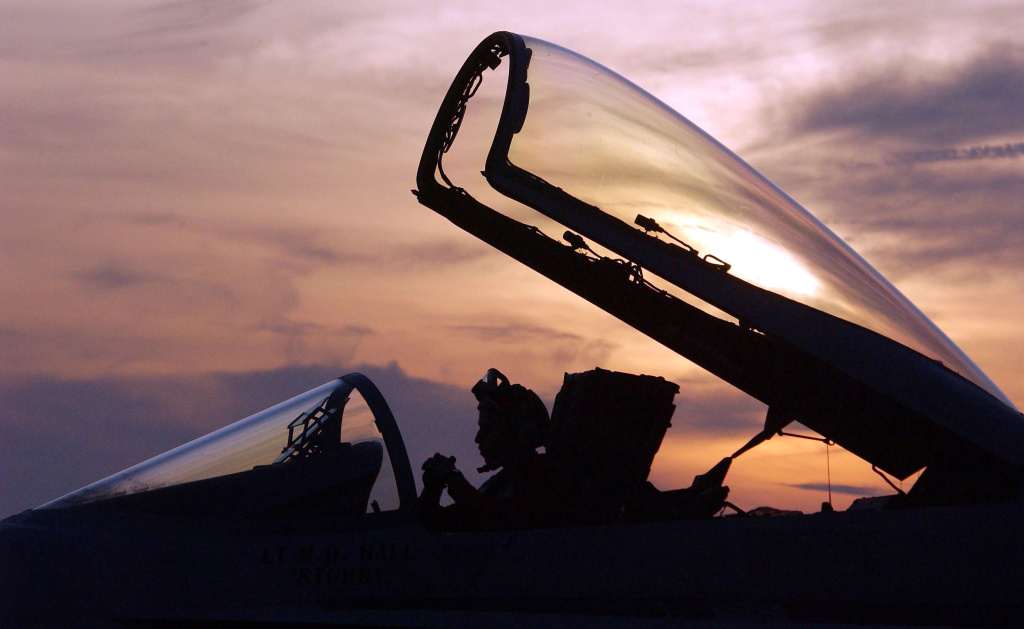 A U.S. Navy flight crewman works in the cockpit of a U.S. Navy F/A-18 Hornet after returning to base aboard the USS Constellation.