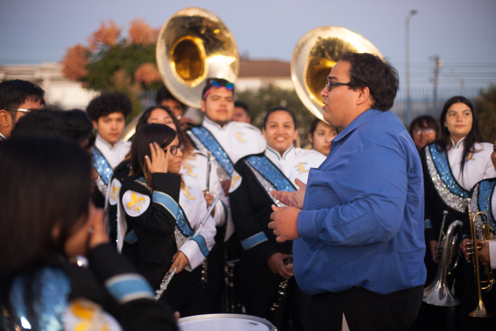 Band co-director Matthew Stickman speaks to band members at the Locke High School homecoming game.