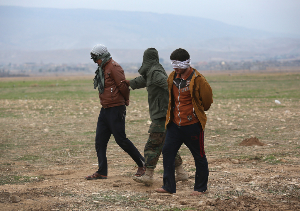 Kurdish Peshmerga forces detain suspected members of ISIL, or Daesh in Arabic, who mixed with a group of villagers fleeing the frontline to a Kurdish-controled area on November 16, 2015 to Sinjar, Iraq.