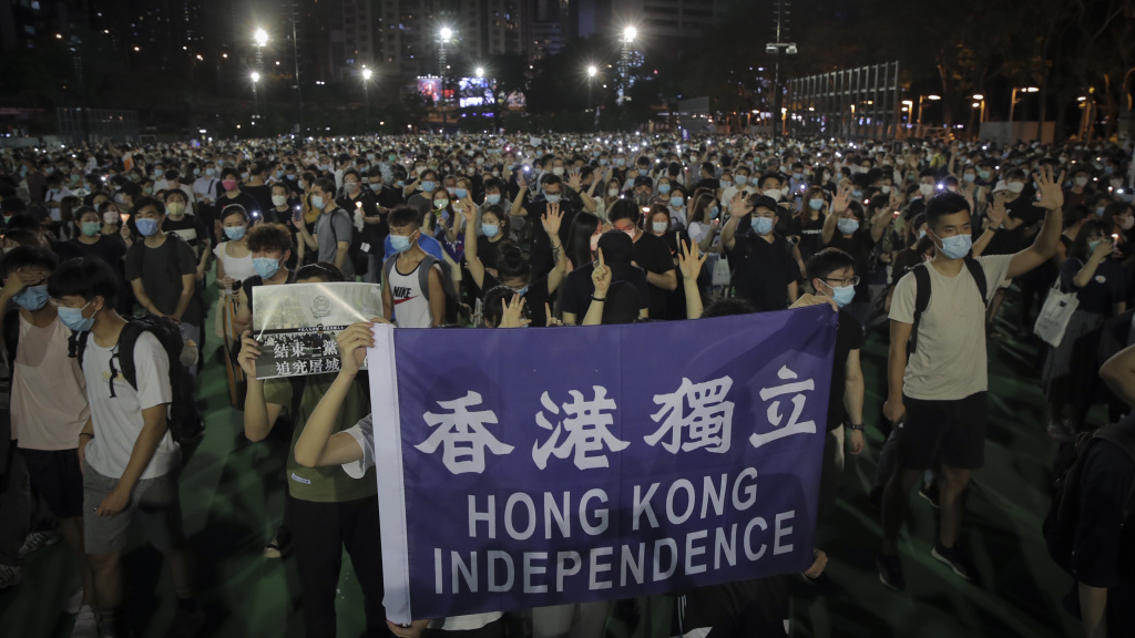People attending a vigil for the victims of the 1989 Tiananmen Square massacre hold a banner reading