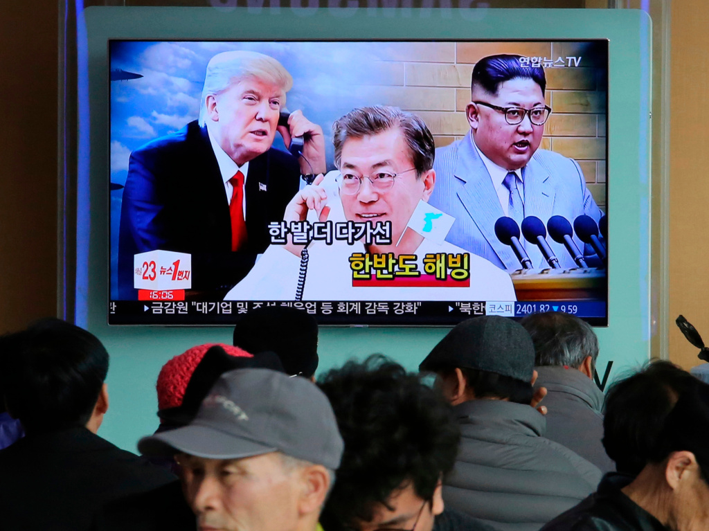 People watch a TV showing images of North Korean leader Kim Jong Un (right), South Korean President Moon Jae-in and U.S. President Donald Trump — and the words