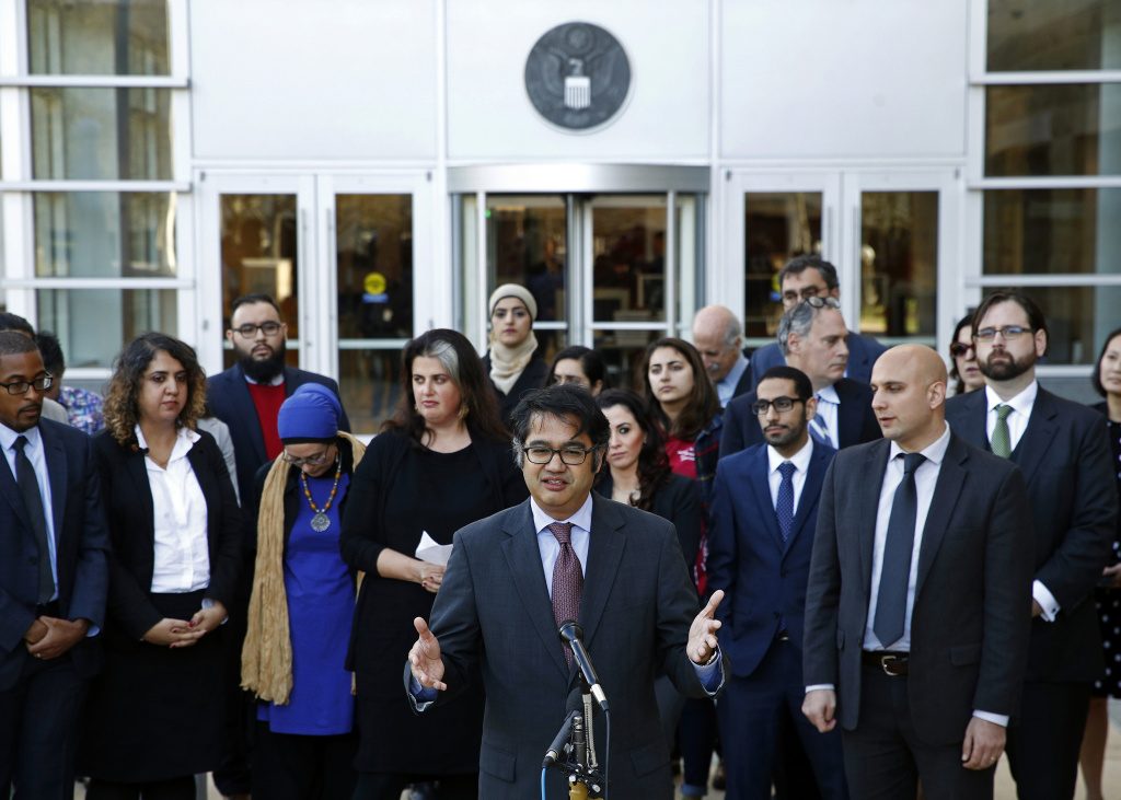 Omar Jadwat, center, director of the ACLU's Immigrants' Rights Project, speaks at a news conference outside a federal courthouse in Greenbelt, Md.