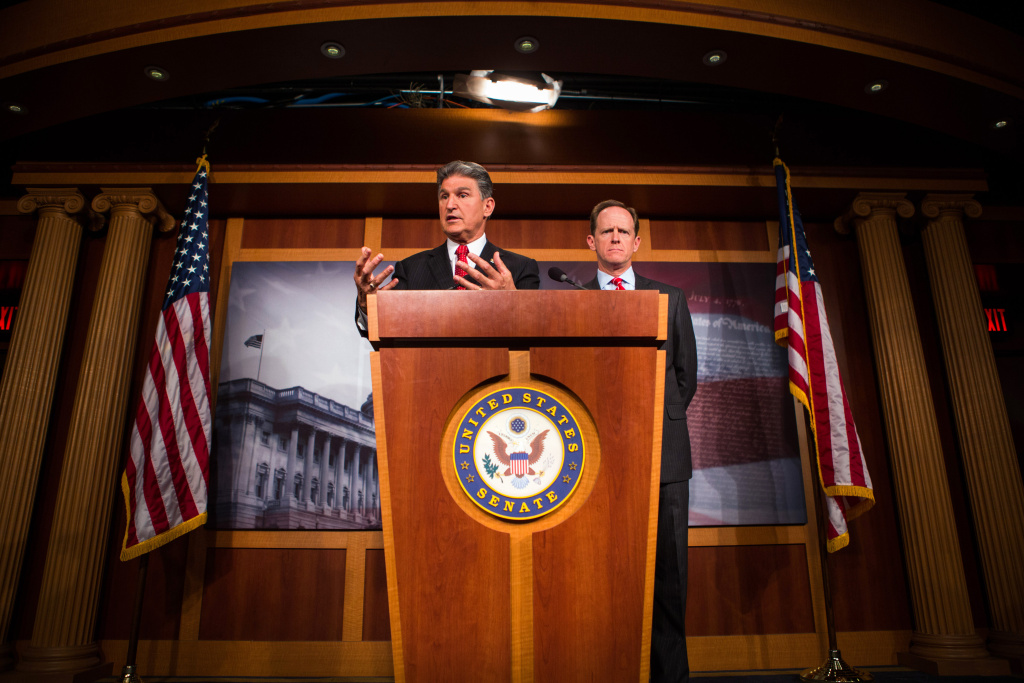 Senators Pat Toomey (R-PA) (R) and Joe Manchin (D-WV) speak to the press in Washington DC on April 10, 2013 about their proposal to expand background checks to firearms sales at gun shows and on the Internet.