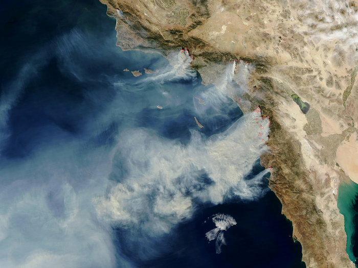 More than 10 wildfires burned over 200,000 acres in Southern California in October 2003, many of them started by humans. This satellite image shows strong winds carrying smoke over the Pacific.