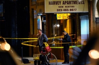Los Angeles Police Department detectives stand outside the Harvey Apartments on Dec. 1, 2010 in Los Angeles. According to reports, a suspect thought to be connected with the murder of publicist Ronni Chasen, fatally shot himself in this Hollywood hotel.
