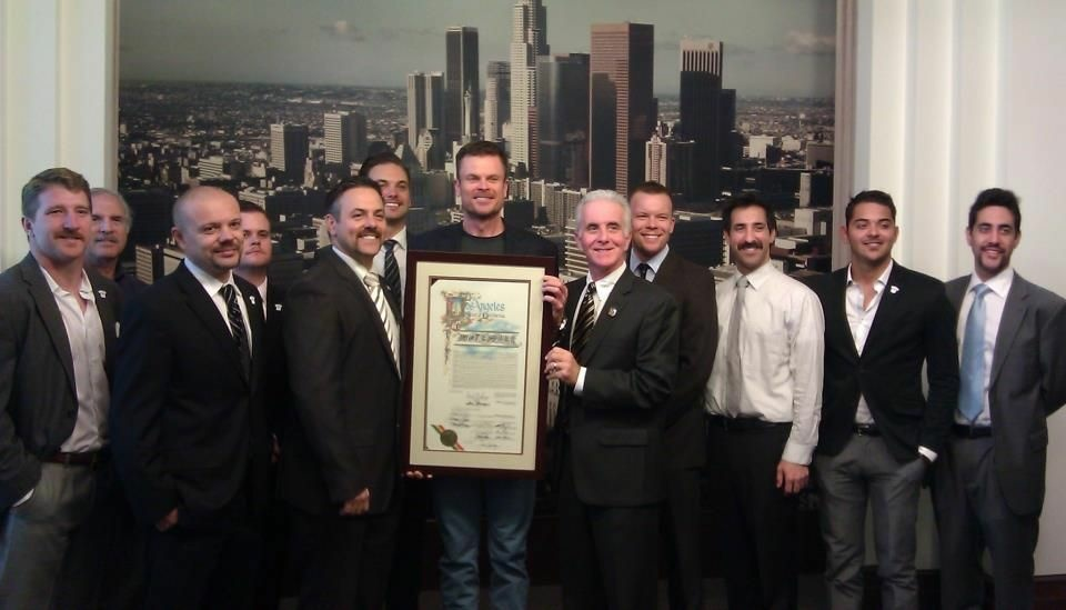 Los Angeles City Councilmen Joe Buscaino and Paul Krekorian, surrounded by the men of their offices, present a city proclamation to Movember, a campaign to draw attention to prostate and testicular cancers.