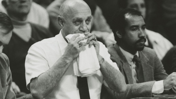 Basketball Coach Jerry Tarkanian chewing on a towel during a game out of superstition.