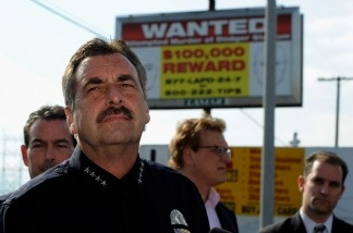 LAPD Chief Charlie Beck stands in front of one of 300 billboards showing a wanted poster for two suspects for the beating of a San Francisco Giants fan Bryan Stow.