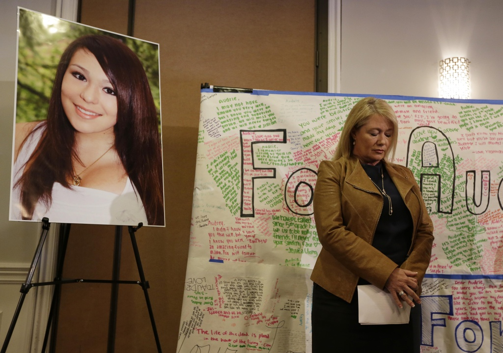 Sheila Pott, mother of Audrie Pott who committed suicide after a sexual assault, stands by a photograph of her daughter and message board during a news conference Monday, April 15, 2013 in San Jose, Calif. The family of a girl who committed suicide after she was sexually assaulted and a photo of the act was shared in text messages said Monday the three 16-year-old boys responsible were sober when the assault happened.