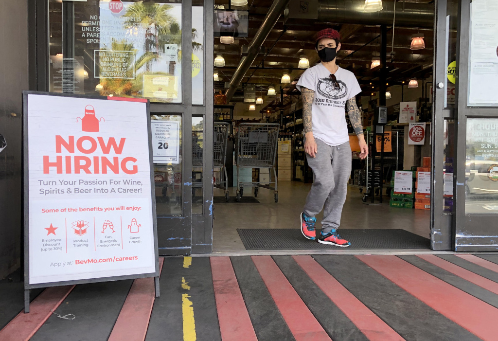 A customer walks by a now hiring sign at a BevMo store on April 02, 2021 in Larkspur, California. According to a report by the Bureau of Labor Statistics, the U.S. economy added 916,000 jobs in March and the unemployment rate dropped to 6 percent.