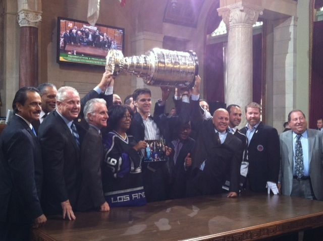 Luc Robitaille lifts up the Stanley Cup, surrounded by members of the Los Angeles City Council.