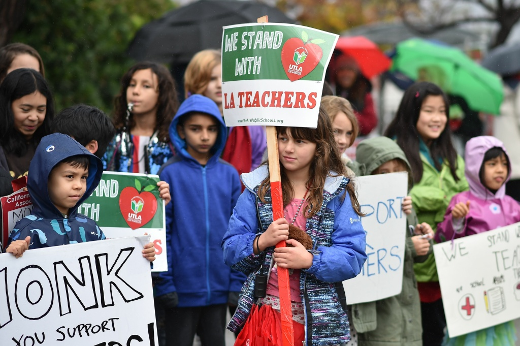 Students pose for a snapshot after walking the picket line with their teachers and parents during the LAUSD teachers' strike, January 16, 2019, outside Dahlia Heights Elementary School in the Eagle Rock section of Los Angeles, California.