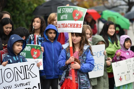 Students pose for a snapshot after walking the picket line with their teachers and parents on the third day of the teachers' strike, January 16, 2019, outside Dahlia Heights Elementary School in the Eagle Rock section of Los Angeles, California.