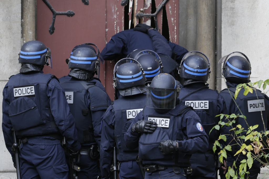 Policemen breaks a door to enter a church in the northern Paris suburb of Saint-Denis city center, on November 18, 2015, to secure the area after French Police special forces raid an apartment.