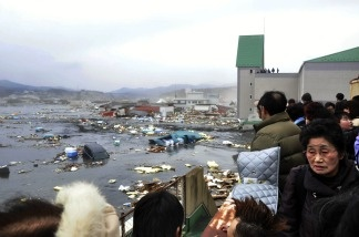 Local residents watch the devastation provoked by a tsunami tidal wave smashing vehicles and houses at Kesennuma city in Miyagi prefecture, northern Japan on March 11, 2011.