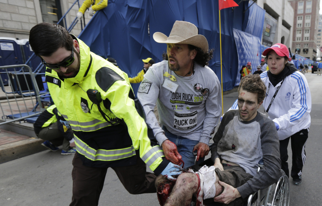 Medical responders run an injured man past the finish line the 2013 Boston Marathon following an explosion in Boston, Monday, April 15, 2013. Conspiracy theorists spread rumors that the man was an