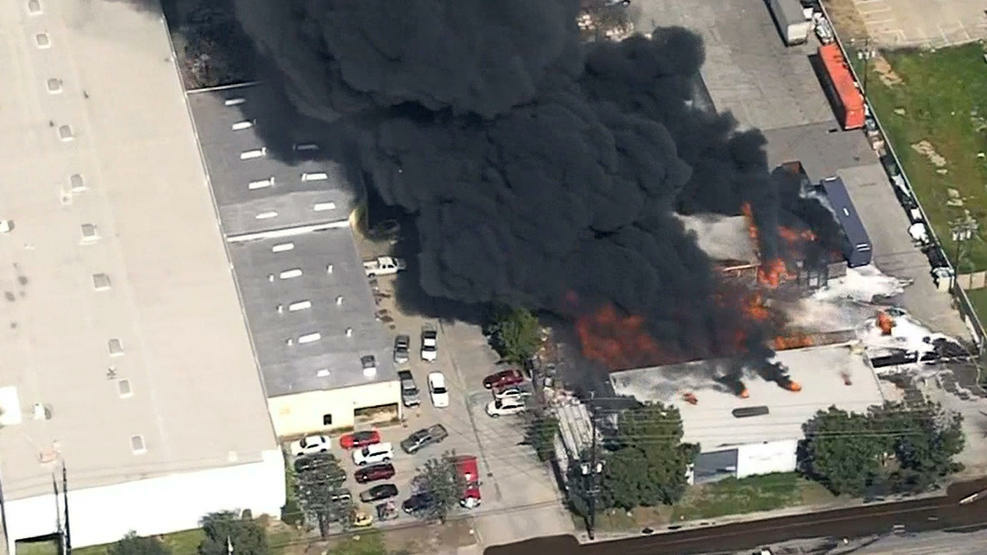 Thick, black smoke billows from a Santa Fe Springs plastics recycling facility on March 13, 2017, after a truck crashed into a power pole and fire hydrant, triggering a fire at a business complex. Several buildings and parked cars caught fire.