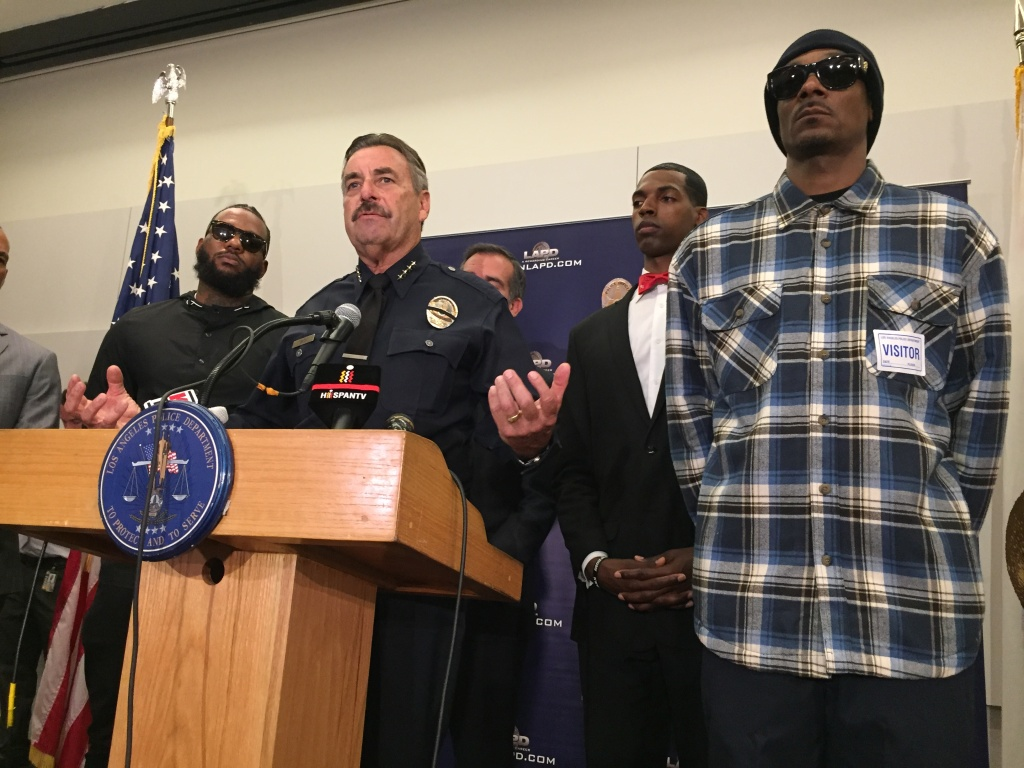 Los Angeles Police Chief Charlie Beck, center, with rappers The Game (left) and Snoop Dogg (far right) at a news conference following a meeting at police headquarters in Los Angeles Friday, July 8, 2016. The rappers led a peaceful march where they urged improved relations between police and minority communities in the wake of shootings in Dallas that left five police officers dead.