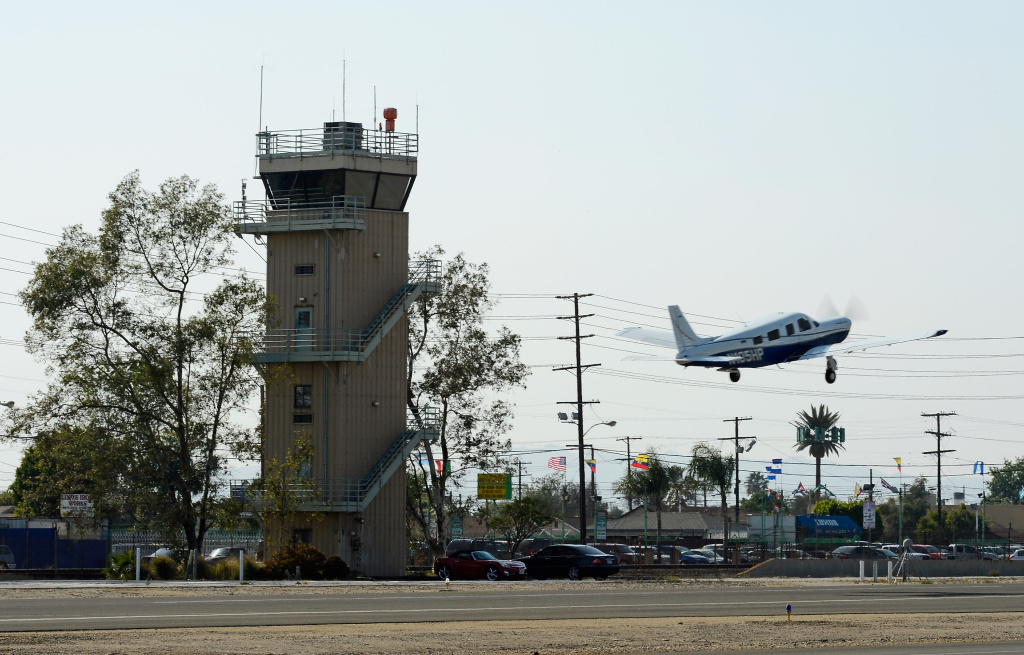 A plane passes the Whiteman Airport control tower as it takes off on March 22, 2013 in Los Angeles, California.