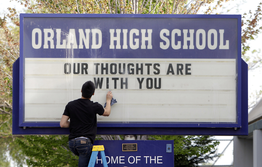 Sergio Parra, 16, a 10th grader at Orland High School, cleans the glass on the school's sign, Friday, April 11, 2014, after placing a memorial remembering the victims of a fiery crash between a tour bus and a FedEx truck in Orland, Calif.