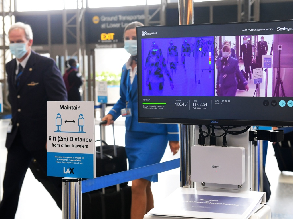 Flight crew walk past thermal cameras that check passengers' body temperatures at Los Angeles International Airport on June 23. As businesses look to reopen, technology firms are offering an array of monitoring systems to try to control the coronavirus.