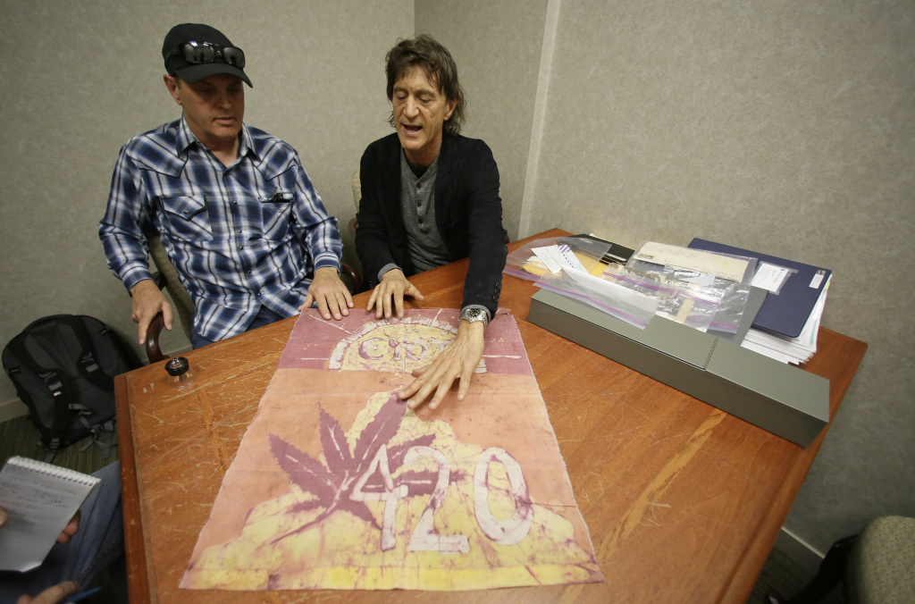 In this Friday, April 13, 2018, photo, Waldos Dave Reddix, left, and Steve Capper look over a 420 flag from 1972 made by a classmate that is kept at a bank vault in San Francisco. Friday is April 20, or 4/20. That's the numerical code for marijuana's high holiday, a celebration and homage to pot's enduring and universal slang for smoking. And five Northern California high school stoner buddies widely credited with creating the shorthand slang for getting high nearly 50 years ago now serve as the day's unofficial grand masters.