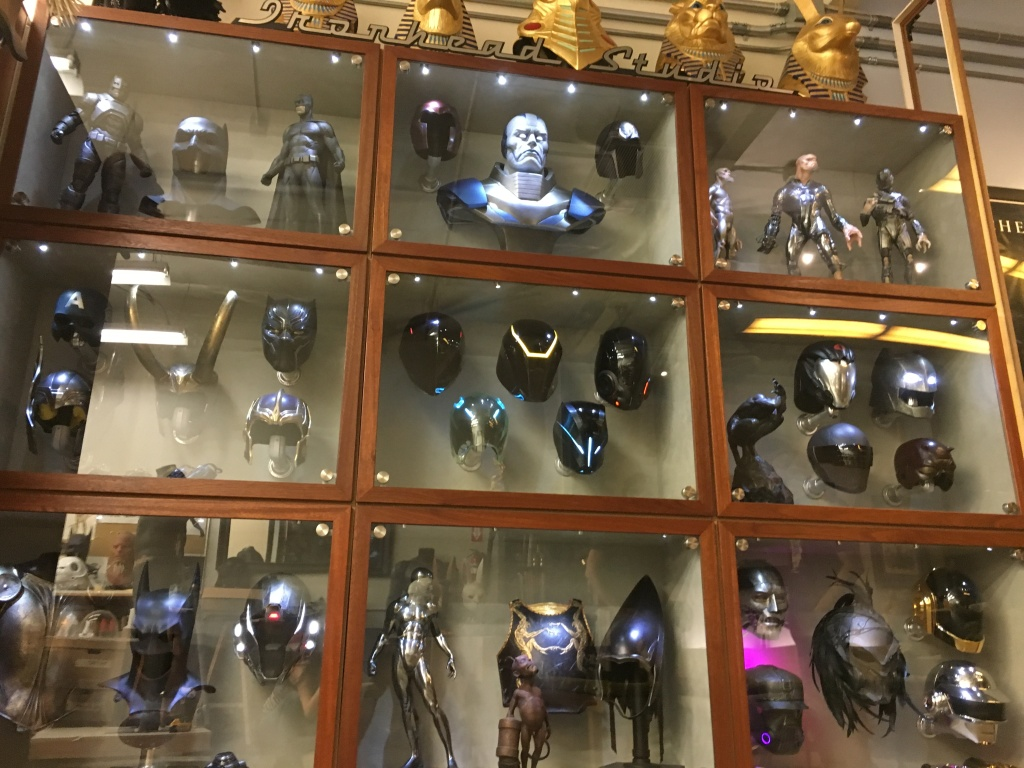 Ironhead Studio Display Case includes superhero headpieces,  DJ helmets, and action figures.